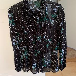 Sælger denne Ganni skjorte  Str S, men en M ville også kunne passe den  Der er lidt fryns på brystet  Prikket mønster med blomster  Røgfrit hjem En enkel knap ved hver håndled