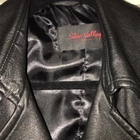 Superfed skindfrakke i meget god kvalitet, fra firmaet Skin Valley, str 42 men mere en l/40 i min optik. Aldrig brugt, virkelig flot slank trenchcoat model.
