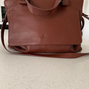 Sælger min dejlige adax taske, da job kræver en ny taske til bærbar pc.   Købt efterår 2018 Mange rum, god størrelse, kan rumme ipad bl.a. Farven er en mellemting mellem mørkebrun og cognac.  Fra hjem uden dyr og røg.