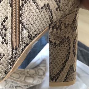 Ankelstøvler fra NLY Shoes Slangeskindsmønstret kunstlæder Spids tå Lukkes med lynlås på den ene side Beklædt blokhæl Hæl 10 cm Højde på skaft 13 cm Omkreds på skaft 25 cm