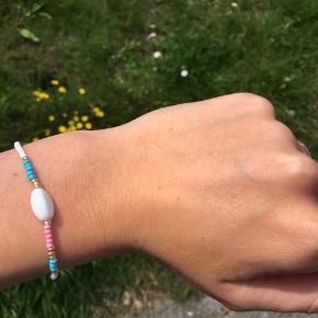 Hjemmelavet armbånd. Kan laves i forskellige farver og med eller uden den hvide perle. Prisen afhænger heraf.