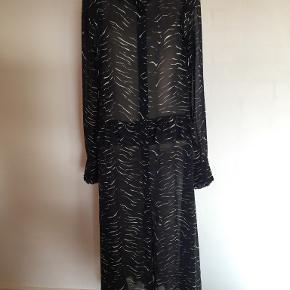 Smart lang kjole, kun brugt 2 gange. Fremstår derfor som ny. Farven er i bundfarve sort med blå og hvide mønstre. Nypris: 450 kr.  Sender med DAO - portoen er 36 kr. som køber betaler, betaling via mobilepay. Se også mine øvrige annoncer. (10)