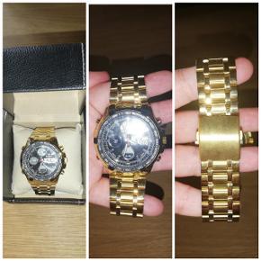 Herre ur i guld Ubrugt herre ur Uret er med forskellige funktioner  brugsanvisning på hvad det kan Medfører.  Æsken som ses på billedet medføre Uret sælges til 200,-   uret var ment som en gave men faldt ikke lige i modtages smag derfor det sælges
