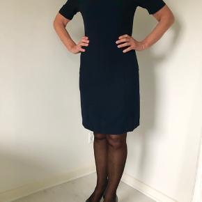 Tidsløs kjole i marineblå str. 34 med korte ærmer fra Selected Femme.  Der er to lommer foran, som fortsætter om på siden.  Lukkes med lynlås i ryggen.  Der er en dejlig blød underkjole.  Længde fra skulder er 89 cm, brystmålet er 88 cm, og taljen måler 74 cm.  Fremstillet af polyester.  Bærer ikke præg af brug.