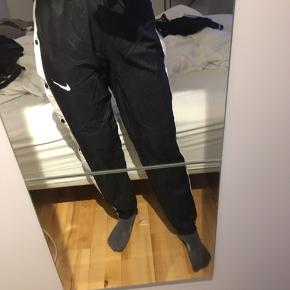 Nike tracksuit bukser samme stand som købt. De har kan strammes alt efter hvilken talje størrelse man har. Ud over det er der knapper i siden som kan knappes op som vist på billedet😊