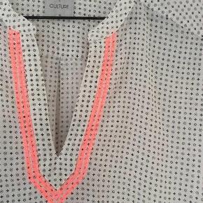 """Varetype: Tunika Farve: Hvid /sort Prisen angivet er inklusiv forsendelse.  Fin let bluse fra Culture  Hvid bund med sort mønster .  Pink syninger ved udskæring  Købt den som """"brugt få gange """"   en anelse fnuller under ærme   brystvidde 2 x57  NU NEDSAT ... og prisen er incl porto"""
