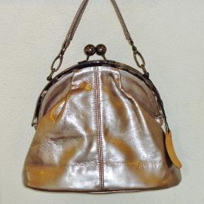 """Sej taske i bronzefarvet """"skind"""". Med indvendig lommer bl.a. til mobiltelefonen.  Bredde: 27 cm Højde: 21 cm Tykkelse/dybde: 10 cm  Ingen byt og prisen er fast."""