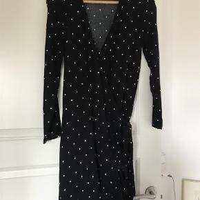 Varetype: Mini Farve: Sort Oprindelig købspris: 600 kr. Prisen angivet er inklusiv forsendelse.  Rigtig lækker slå-om kjole fra Samsøe & Samsøe, sort med hvide pletter. Ikke brugt mere end 2 gange.