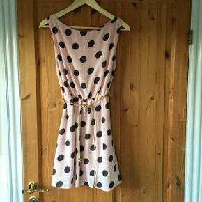 Italiensk kjole uden ærmer med elegant, bred halsrunding, inderfoer, pudder-rosa med sorte prikker. Flettet guldbælte til. Str. 14-16 år. Sender gerne ved samlet køb for min. 100 kr.