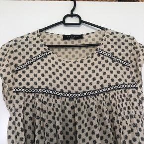 Fremstår som ny.  Meget tynd og let kjole i blødt og behageligt stof. Sort mønster i kjolen og sort/beige bånd rundt  på overdelen.