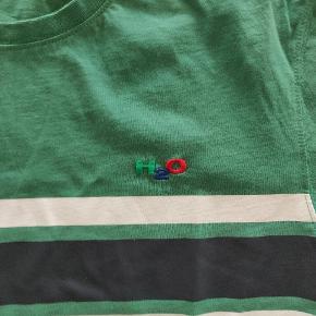 Varetype: T-Shirt  Farve: Grøn, sort og hvid   T-shirt fra H2O, detalje med tre striber hen over brystkassen og mærket H2O oven over.