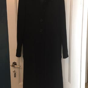 flot lang sort frakke fra Hennes str. 44, yderstof 35% uld, 35% acryl, 25% polyester. Meget lidt brugt - fin stand. Længde 115cm. (Hende der har den på på billedet, er kun en str. 38 og 164 høj, så den er selvfølgelig for stor). 300kr Kan hentes Kbh V eller sendes for 40kr DAO