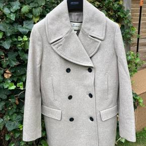 Klassisk uldjakke / uldfrakke i fin stand i 80% uld. Ca. 80 cm. Den har 2 lommer med klap, der stadig er riet til, da jeg ikke har brugt lommerne. Desuden er der 2 skrålommer foran, der er god til at varme hænderne på en kold dag. Passer også en str 36. Røgfrit hjem. Sendes med DAO