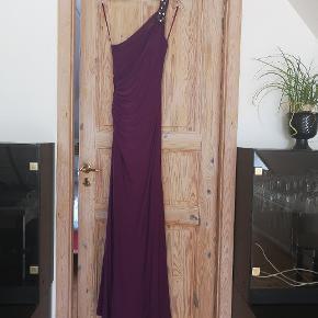 UBRUGT GALLAKJOLE FRA LILLY STR. 36 Denne kjole er købt i december 2015 og meningen var at den skulle bruges til galla. Jeg fik den aldrig brugt, så nu hænger den flotteste kjole med prismærke på bare i mit skab. Den har den smukkeste lilla farve, er tætsiddende og rucheret i den ene side ved taljen. Den har rhinsten over den ene skulder samt den flotteste bryderryg. Det er virkelig et fund, og jeg havde selv beholdt den hvis jeg troede på at jeg ville få den brugt. Nypris var 2200kr, men jeg vil egentlig bare gerne finde en heldig ejer til den, så jeg er villig til at gå langt ned i pris. Der medfølger original dustbag, pose og bøjle.