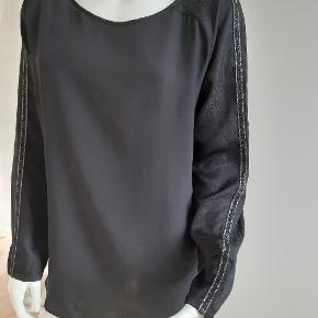 Varetype:Super flot langærmet bluse i 100% silke. Flot stribe ned af ærmet Farve: sort Matriale: 100 % silke Brystvidde 2 x 56 cm Længde: 65cm Nypris: 1399