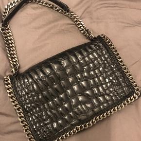 Skind taske fra Zara med justerbar strop; den kan både være kort som en håndtaske og lang som en crossbody (se de to billeder). Med trykknap og en skillevæg indvendig, der deler tasken i to rum. Desuden en indre åben lille lomme til dankort el lign.   Aldrig brugt  Ny pris: 900 kr  Skal afhentes i Købehavn.