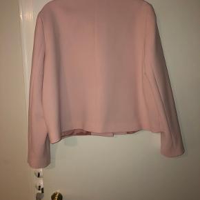 Sand lyserød kort jakke med lyserøde knapper med guldkant. Formentlig størrelse 40, men mærket mangler. Brugt få gange.