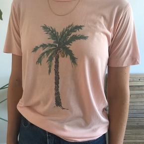 Fin lyserød/ferskenfarvet t-shirt i 67% lyocell og 33% bomuld.