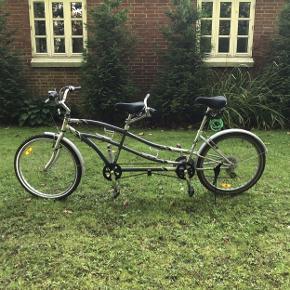 Som billederne viser, er det en tandem cykel, hvilket medfører, at der kan være 2 personer der cykler samtidigt. Der følger en lås og nøgle med, som der også kan ses på ét af billederne. Der er 3*7 gear på cykelstyret forrest. Der medfølger små cykellygter både foran og bagpå. Der er to drikkedunkholdere, som der også kan ses på ét af billederne.