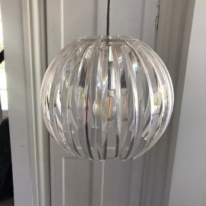 Fin lampe i transparent plast. En af pindene har været knækket, men er limet på og ses ikke når ophængt  Afhentes i Holte