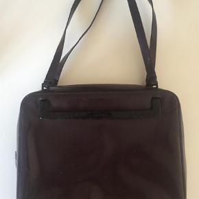 Varetype: Taske  Størrelse: M Farve: Brun  Vintage Gucci taske i brunlig/blomme farve. Skrammer diverse steder men ellers intakt. Arvestykke og kender derfor ikke yderligere detaljer. Forvent ikke en ny taske men den har mange år endnu. Kan bæres over skulderen men ikke crossbody. 30cm lang og 24cm bred.