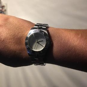 Rigtig fint ur fra MJ. Der medfølger original æske og ekstra led.   Uret har små brugsridser på rem som ikke kan undgåes ved brug.   Der er desværre kommet mindre ridser i glasset i den ene side. Uret skal også have nyt batteri. Derfor også den meget billige pris.  Man kan vælge at leve med det, da man sagtens kan se hvad klokken er og de ikke på den måde er generende eller voldsomt tydelige når det er på (se billede 3)   Man kan også få skiftet glasset - koster ca 300 kr ved urmager. Vælger man den løsning har man stadig et rigtig billigt MJ ur??  Nypris ca. 1695 kr.   Armbåndsur Farve: Sølv Oprindelig købspris: 1695 kr.