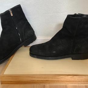 Varetype: Støvler Farve: Sort  Lækre og meget komfortable Chelsea boots fra det danske mærke, Last Conspiracy.  Støvlerne er håndsyet i Portugal og overdelen er lavet i sort ruskind. Sålerne er lavet i læder og gummi og sålen er randsyet.   Er kun brugt få gange, og de er passet meget godt på og er naturligvis opbevaret med skolæster. Skolæster følger ikke med ved salg.   Størrelse 45 (bruger selv 44, men med en kraftig uld-sål, så går det fint).  Giv et bud!  Mvh. Morten