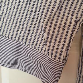 """Lang skjorte i lige facon, med blå og hvide striber. Ved krave og ærmekanten er stoffet """"glat""""."""
