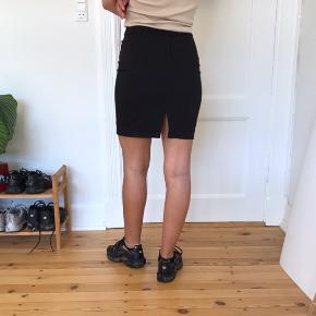 Tætsiddende sort nederdel fra H&M, str. 34. Lille slids. Lukkes med lynlås bagpå.