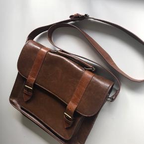 Fed taske i imiteret læder. Har er stort rum og rum i indersiden. Remmen kan justeres, måler 25x 30 cm  Bytter ikke  Se også mine andre annoncer 🌺