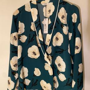 Nypris var 600 og den er aldrig brugt Skjorten er mere en mørkegrøn farve end hvad den ser ud på billederne. Der er knapper som lukker pænt i bunden af skjorten