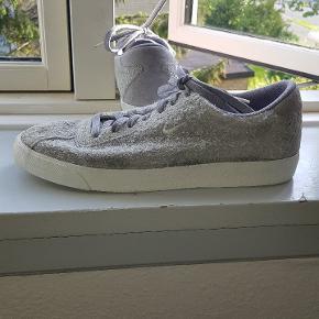Nike sneakers i grå med noget af skoen i en slags pelset materiale. Str 45 ½ Cond 6.5/10 Mødes i århus/hadsten eller sendes for 50kr
