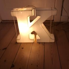 Lampe i mat porcelæn formet som et K. Lampen kan både stå og hænges op.  Str: Højde: 31 cm Bredde: 36 cm Dybde: 9 cm