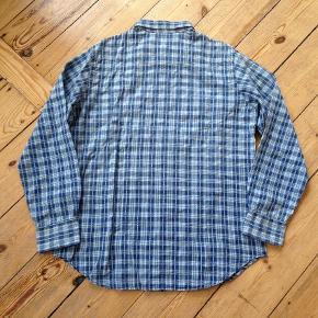 Varetype: Lækker skjorte i bomuld Farve: Blå/hvid Oprindelig købspris: 1000 kr.  Brugt 2-3 gange - fremstår som stort set ny. Fejler intet.  Lukkes med trykknapper  Materiale: 100% cotton  Mål: Længde fra nakke og ned: Ca 76 cm Brystvidde: ca 2x59 cm Skulder til skulder: ca 46 cm  Bytter ikke   *** se også mine andre annoncer med mærkevarer ***