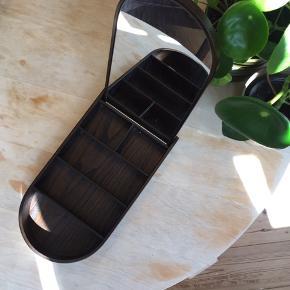 Smykkeskrin med indbygget spejl fra Menu sælges. Mener det er eg med brun bejdse. Det har fået en lille skade i fineren, hvor man sætter spejlet i (se foto), men det er ikke noget man bemærker. Ellers fin stand.  Bytter ikke. Kan ses på Islands Brygge, Kbh S.   Ønskes TS-handel betaler køber gebyrerne.