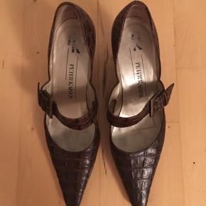 Mega fede Peter Kaiser vintage sko med firkantet snude og elegant lille hæl samt spænde hen over vristen. De er lavet i det lækreste krokodilleprægede læder i skøn mørkebrun farve. De er formentlig da slut 90'erne eller start 00'erne. Str UK 6. 100% ægte læder. Kom med et bud.   Varen befinder sig i 9520 Skørping. Sender med DAO.  Se også min øvrige annoncer. Jeg sælger tøj, sko og accessories. Pt er min shop fuld af retro og vintagekup, high street fund og mærkevarer i mange forskellige str. Kig forbi og spøg endelig!!