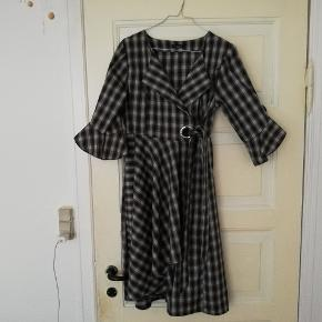 Fin slå om ternet kjole med store ærmer fra Binstyle. Med bindebånd og fine detaljer