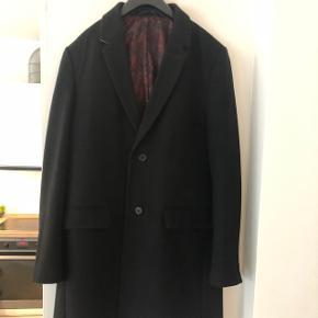 Lækker lang frakke i sort.  Jeg er 178cm og den når mig lige over knæet og sidder ikke løst.