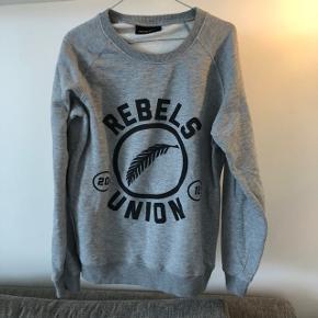 Fed gråmeleret sweater fra Rebels Union Aarhus. Størrelse L. I god stand. Let fnuldret.