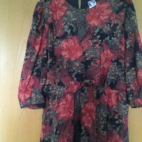 Flot blomstret vintage - retro kjole med elastik i taljen. Kjolen fremstår som ny. Passer en 38-40. Mål: længde 105 cm, talje: 2*36-48 cm, bryst: 2*51 cm.
