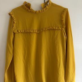 Fin gul bluse der er lidt lang. Brugt få gange, dog er mærket er ved at falde af. Skriv for flere billeder.