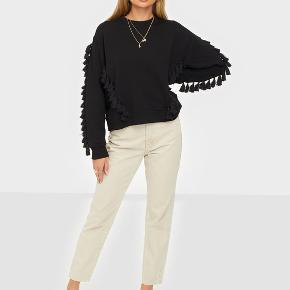 Giv din afslappede sweatshirt et løft med denne frække, korte sweater. Den har kvaster ned ad siderne og ærmerne og har By Malene Birger-navnet broderet oven over venstre bryst. Sweateren er perfekt til en afslappet hyggedag. Materiale: 100% bomuld. Mål str. XXS: bryst 54cm, længde 53cm, ærmelængde 80cm.  Nypris: 1400kr.
