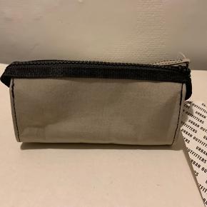 Beige / sand / lys khaki farvet mindre evt kosmetik bag eller til andre small accessories fra UO. Bredde ca 16 cm og højde ca 7 cm Kraftigt materiale i poly/nylon/bomuld (Kan evt muligvis sendes for 20 som brevpost via postnord)