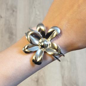 Fint smykkesæt med matchende blomst. Et afdæmpet statement, der matcher alt, især  mere neutrale farver. Armbåndet har en bøjelig fjederlukning, og er nemt at få på. Der er to meget små pletter på armbåndets blomst, hvor belægningen er gået af, men det er ikke noget man ser.