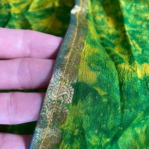 Skøn kimono fra Indien syet i gamle sari'er. Let viscosekvalitet og guldkanter. Passer både str s og str m. Aldrig brugt