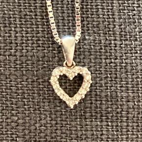 Smukt 14 kt hvidguldshjerte med diamanter.  Kæden er sølv