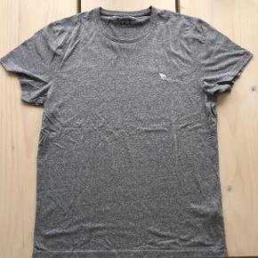 Abercrombie & Fitch basic tee i grå med lille logo. Dejlig tee i flot gråmaleret farve med et lille hvidt logo. God pasform og kun brugt og vasket få gange. Nypris 200 DKK.