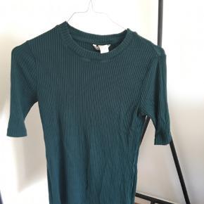 Grøn rib T-shirt. Små slidmærker oppe ved kraven (se sidste billede). Dog stadig brugbar