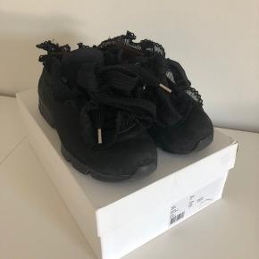 """De populære Ganni sneakers i sort. Den øverste """"lykke"""" til snørebåndet på højre sko er faldet af, så skoene skal derfor snøres et tak længere nede (se billede). Stadig i god stand derudover.   Der medfølger æske. Oprindelig pris: 1.999kr"""