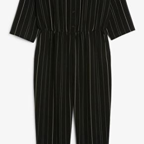 Flot sort buksedragt fra Monki med hvide striber. Den er brugt få gange, men der er kommer lidt fnuller ved den højre lomme - udover det er der ingen tegn på brug  Køber betaler fragt
